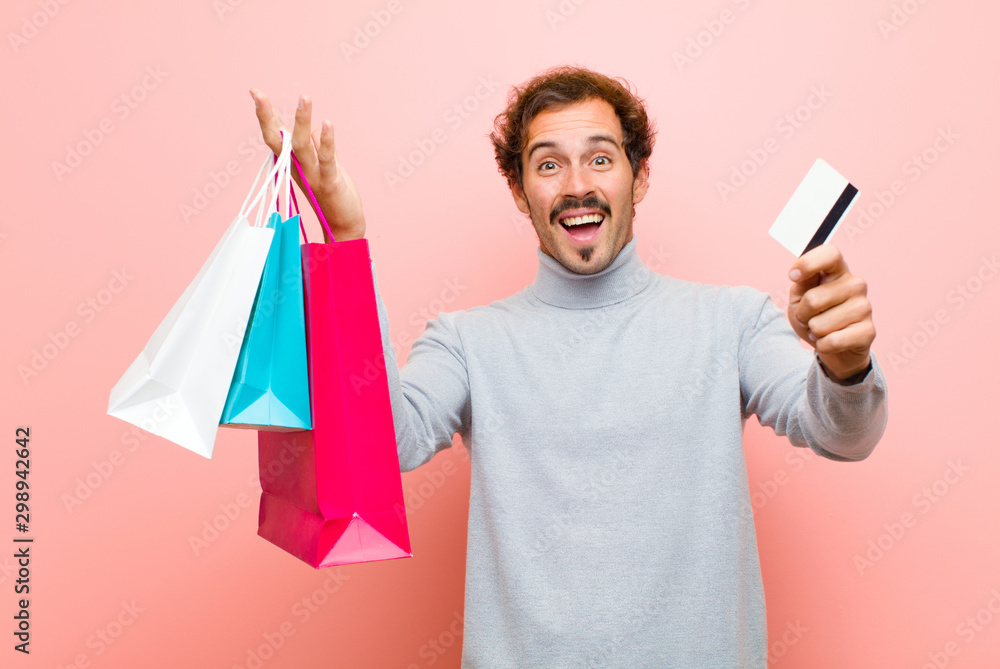 Fototapety, obrazy: young handsome man with shopping bags against pink flat wall