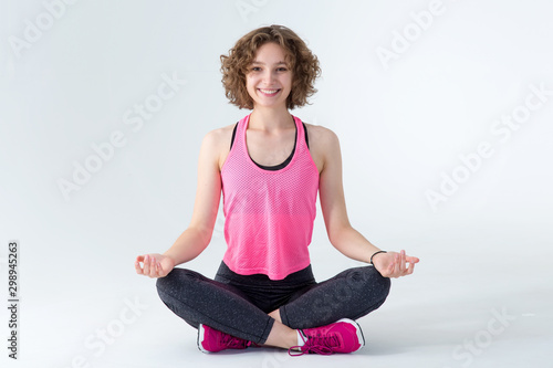 Young fitness woman meditating in lotus position on a gray background.
