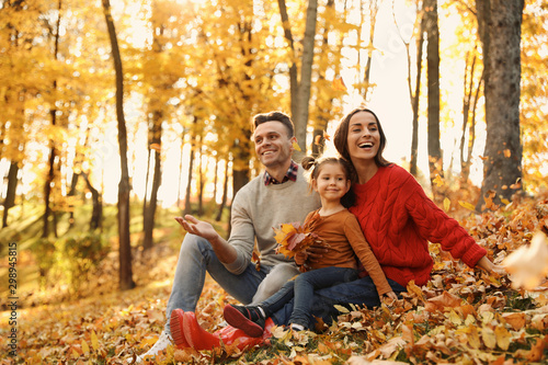 Happy family with little daughter in park. Autumn walk