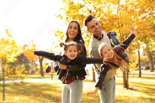 Obraz Happy family with little children in sunny park. Autumn walk - fototapety do salonu