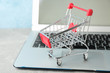 Small shopping cart and laptop on grey background, copy space