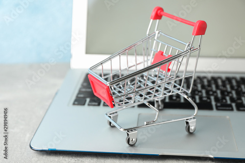 Fotografía  Small shopping cart and laptop on grey background, copy space