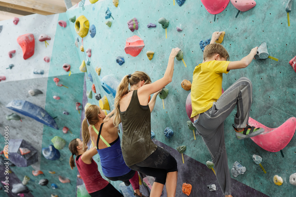 Fototapeta Young sportswomen and schoolboy in activewear creeping upon climbing wall