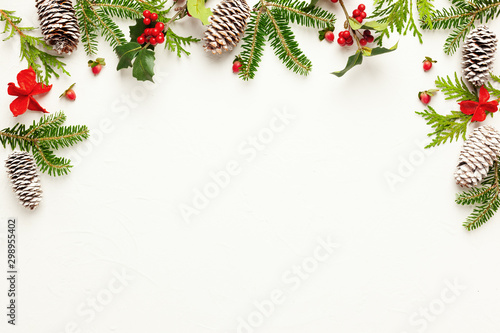 Christmas background with pine cones, branches of holly with red berries and fir tree on white Fototapeta
