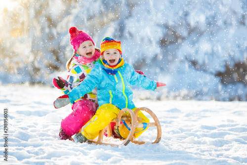 Fototapeta Kids play in snow. Winter sleigh ride for children obraz