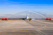 Water Salute By Fire Truck At The Airport For First Visit Passenger Airplane. The Plane Moves Behind The Follow-me-Car