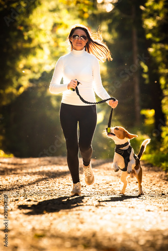 Obraz Girl is running with a dog (Beagle) on a leash in the autumn time, sunny day in forest. Copy space in nature - fototapety do salonu
