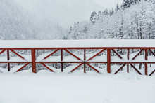 Red Colored Railings On A Bridge Under Blizzard.