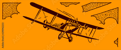 Historical single-engine biplane aircraft flying in front of a cloudy sky on an orange background Canvas Print