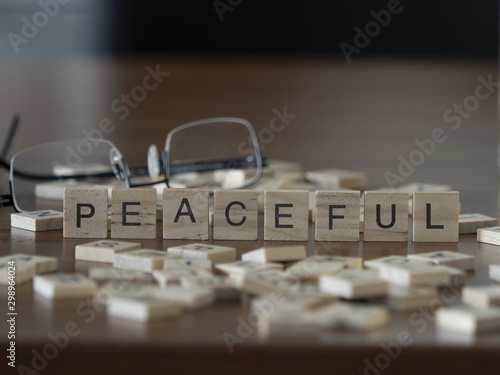 Fotografija  The concept of Peaceful represented by wooden letter tiles