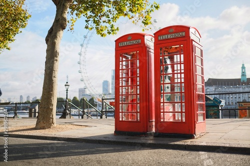 Fotografie, Obraz Two London Telephone Boxes on an Empty Street by the River Thames