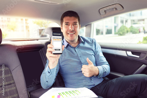 Obraz na płótnie Mature businessman sitting on backseat of car rating taxi services on app while