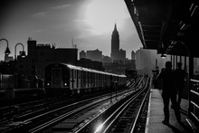 Black And White Shot Of A Railroad Station With People's Silhouettes And City