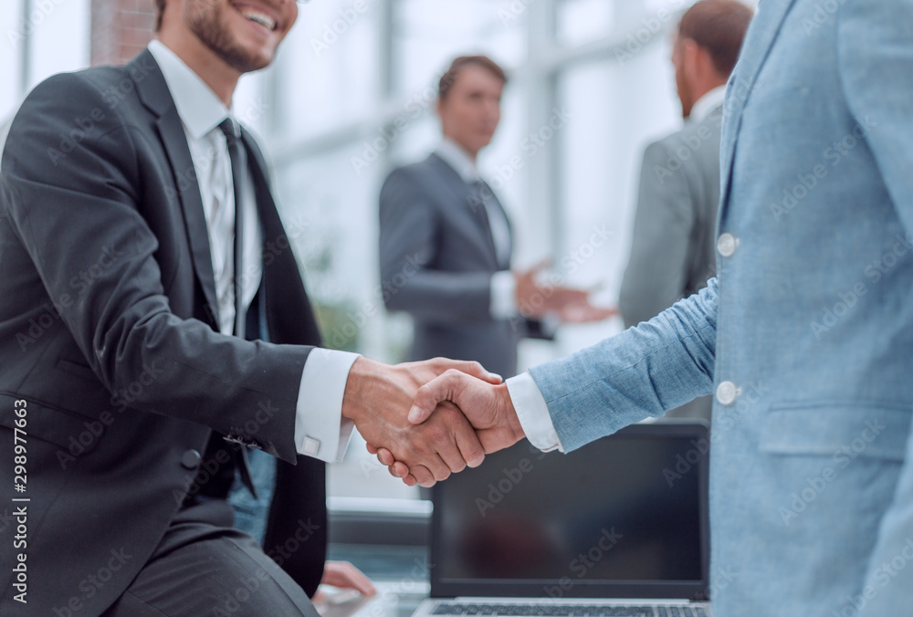 Fototapeta happy young businessman shaking hands with his business partner