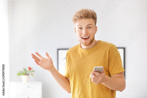 Portrait of happy man with mobile phone at home Canvas Print