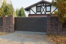 Brown Wooden Gate And Brick Fe...