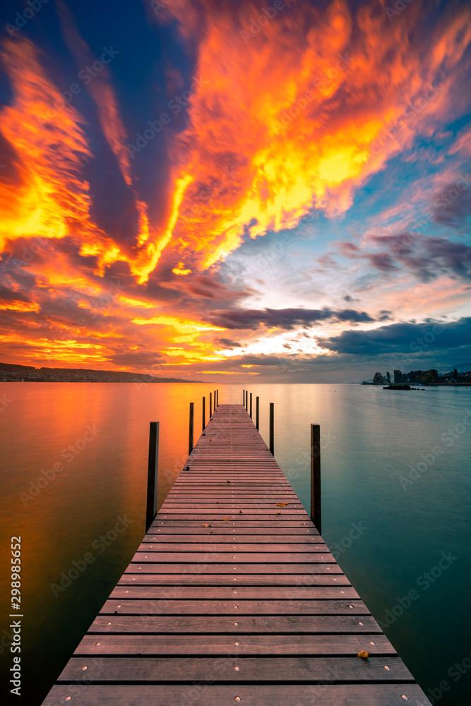 Bootssteg im Abendrot, der Himmel steht in Flammen