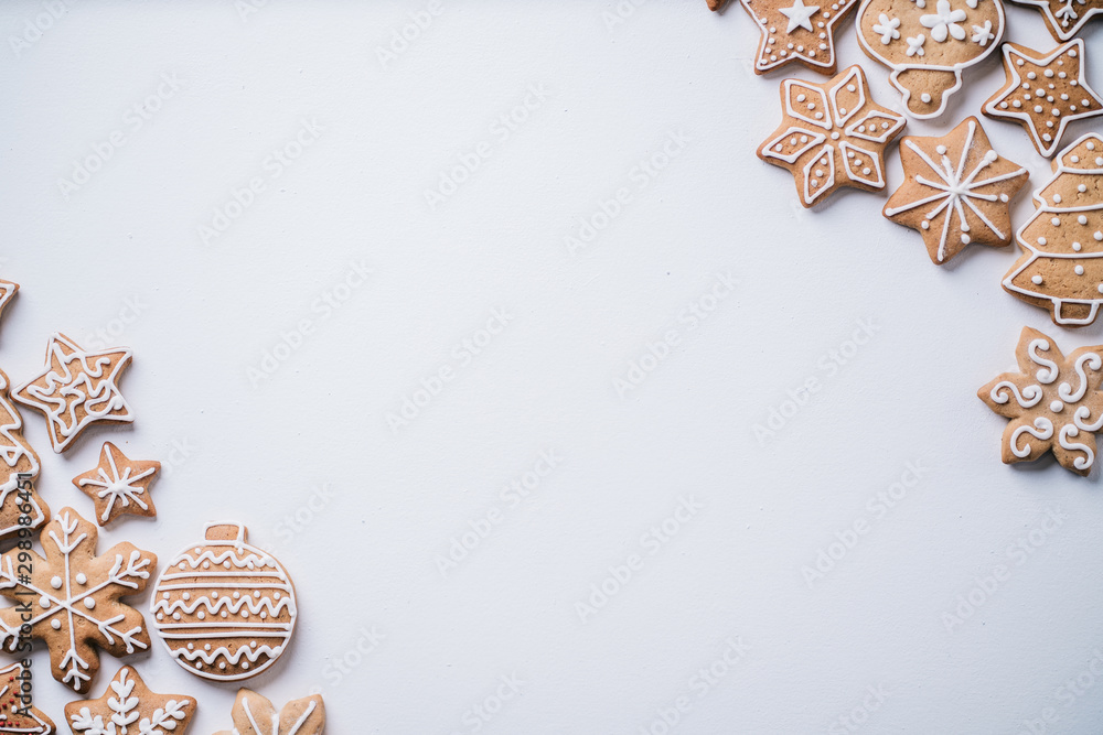 Fototapeta Christmas background with homemade gingerbread cookies on white table, copy space. Festive food, New Year celebration traditions