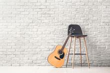 Modern Acoustic Guitar And Chair Near White Brick Wall