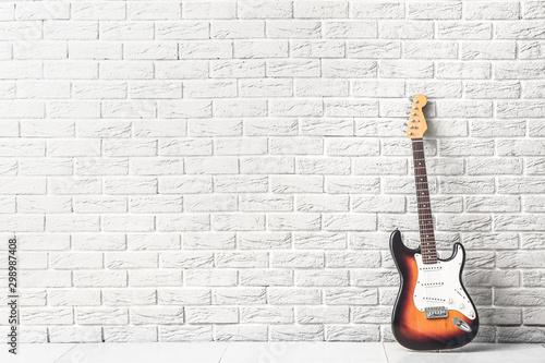 Nowożytna gitara basowa blisko białego ściana z cegieł