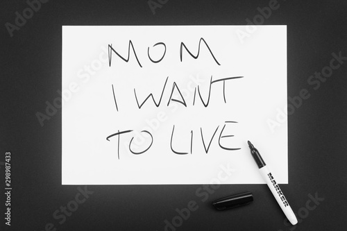 Written in black marker on a white piece of paper: Mom, I want to live Wallpaper Mural