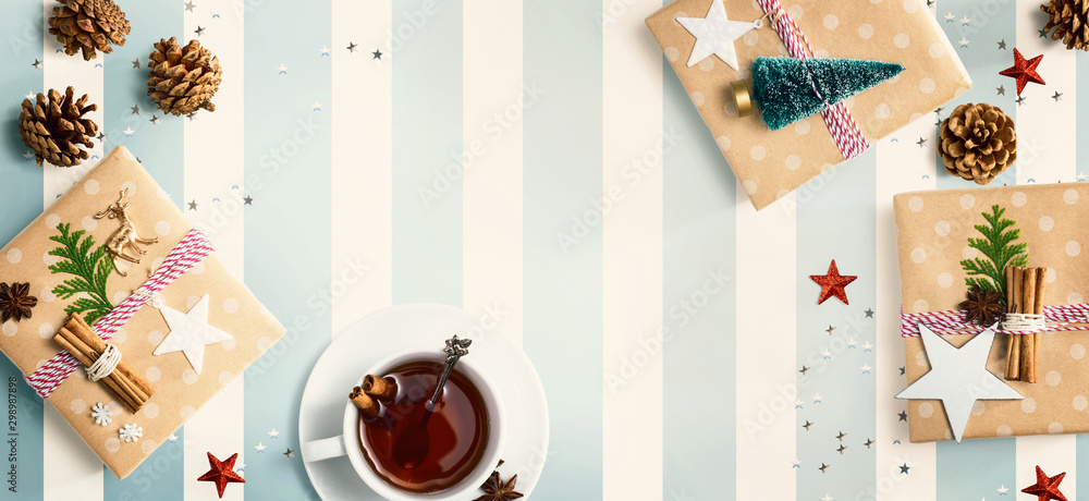 Fototapeta Christmas gift boxes with a cup of tea - flat lay