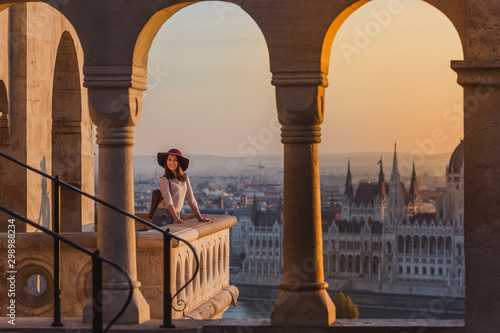 Photo A happy young woman enjoying her trip to the Castle of Budapest in Hungary on the view point from Fisherman Bastion on sunrise