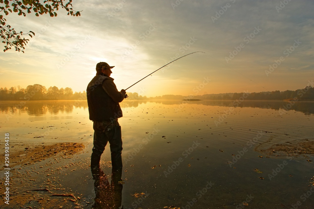 Fototapety, obrazy: angler catching fish in the lake during cloudy sunrise