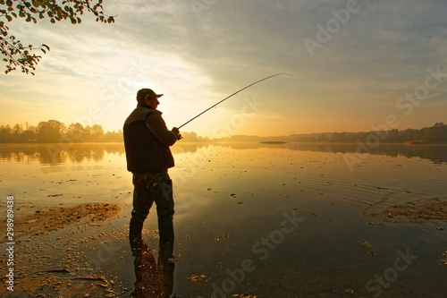 Fotografia angler catching fish in the lake during cloudy sunrise