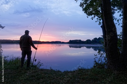 Obraz Silhouette fisherman standing on the shore of the lake during dawn - fototapety do salonu