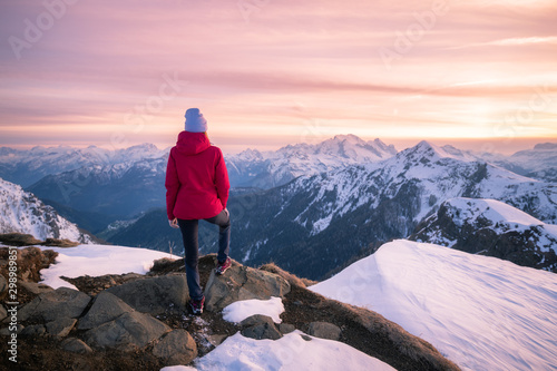 Fototapeta Young woman in snowy mountains at sunset in winter. Beautiful slim girl on the mountain peak against snow covered rocks and colorful red sky with clouds in the evening. Travel in Dolomites. Tourism obraz
