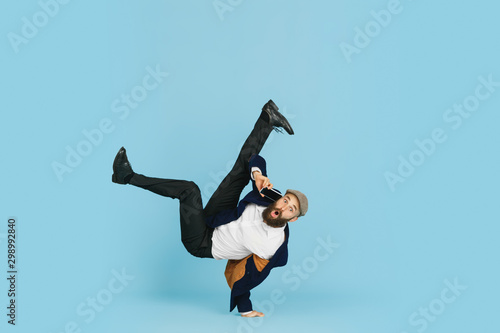 Платно Young caucasian businessman having fun dancing break dance on blue studio background