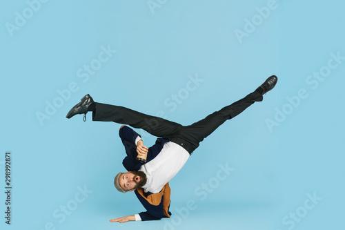 Fotografia Young caucasian businessman having fun dancing break dance on blue studio background