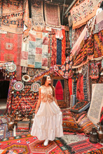 Happy Travel Woman With Amazing Colorful Carpets In Local Carpet Shop ,Goreme. Cappadocia Turkey
