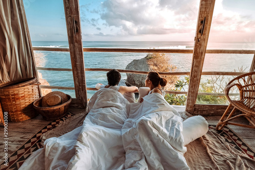 Canvas-taulu Couple enjoying morning vacations on tropical beach bungalow looking ocean view