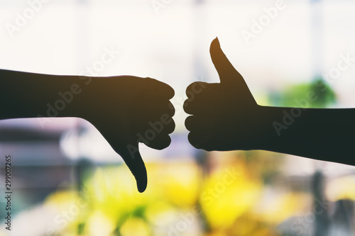 Silhouette image of two hands making thumbs up and thumbs down sign Canvas Print