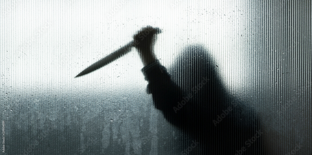 Fototapeta shadow of hand holding big sharp knife behind Frosted glass in the bathroom background.Robber,murderer or killer with knife.concept of scary crime scene of horror or thriller movies,Halloween theme