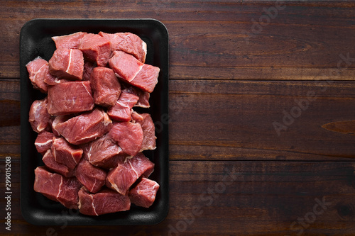 Fresh raw diced red beef meat on cast iron plate, photographed overhead with cop Wallpaper Mural