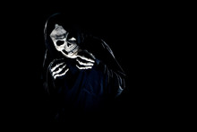 Scary Monster Or Grim Reaper Ghost Coming Out Of The Dark Shadows To Haunt During Halloween.  Depicts A Scary And Deadly Fictitious Demon