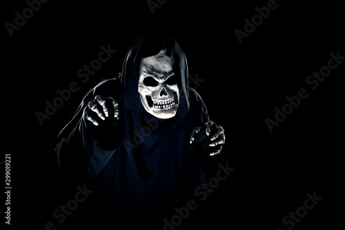 Scary monster or grim reaper ghost coming out of the dark shadows to haunt during Halloween Canvas Print
