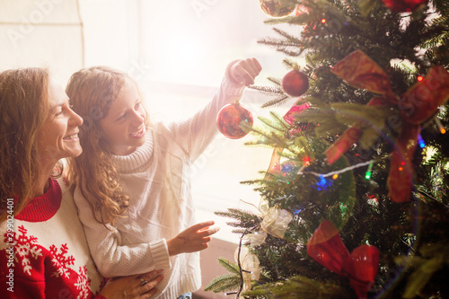 Fotografia  Mom and daughter decorate the Christmas tree
