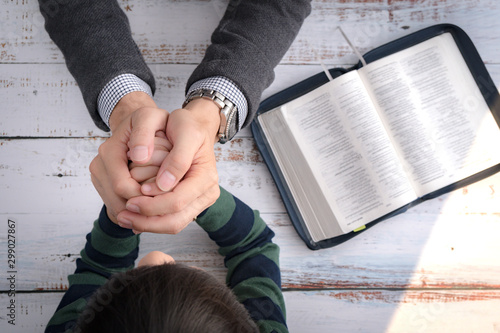 Top view closeup of a father and his little son's hands praying together after bible study in the morning Canvas Print