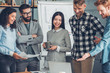 canvas print picture - Startupers working together at office standing looking at laptop screen smiling joyful