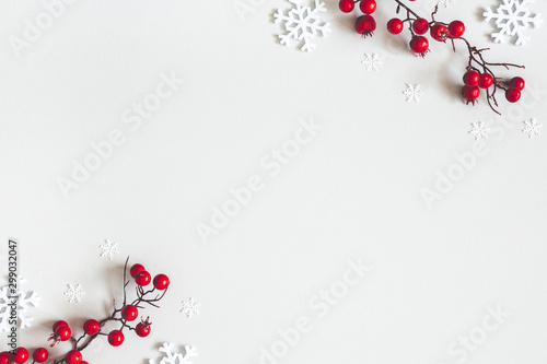 Obraz Christmas or winter composition. Snowflakes and red berries on gray background. Christmas, winter, new year concept. Flat lay, top view, copy space - fototapety do salonu