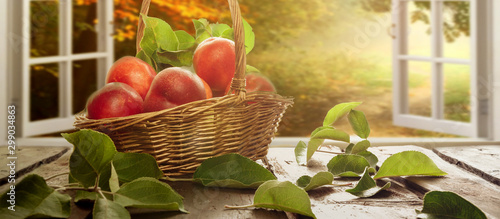 Peaches and nectarines in a wicker basket on a wooden table fruit harvest in a rustic style with a copy space - 299034863