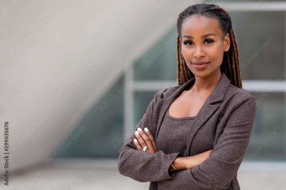 Fototapeta Beautiful female african american business woman CEO in a suit at the workplace, standing confidently with arms folded