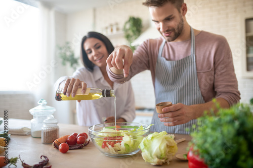 Husband and wife seasoning salad while cooking lunch Fototapet
