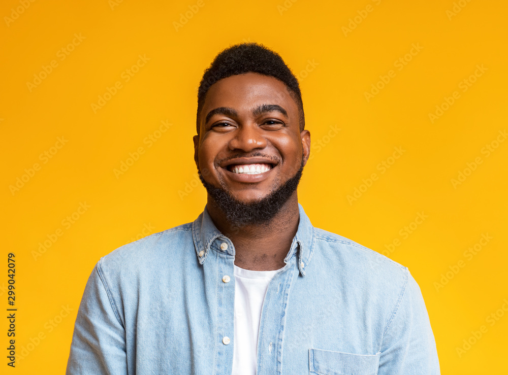Fototapeta Portrait of cheerful bearded black man over yellow background
