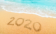 Happy New Year 2020, Lettering On The Beach With Wave And  Blue Sea. Numbers 2020 Year On The Sea Shore, New Years Concept.