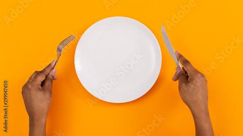 Fotografie, Obraz Black female hands holding empty plate on orange background, top view, free spac